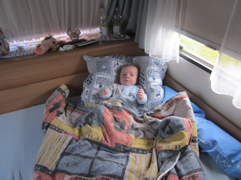 Baby im Campingbett
